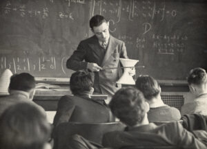 An unidentified mathematics professor, possibly William T. Reid, at the University of Chicago circa 1939, uses a hyberboloid model to discuss the equation written in the upper left of the black board with students. e_math_01104