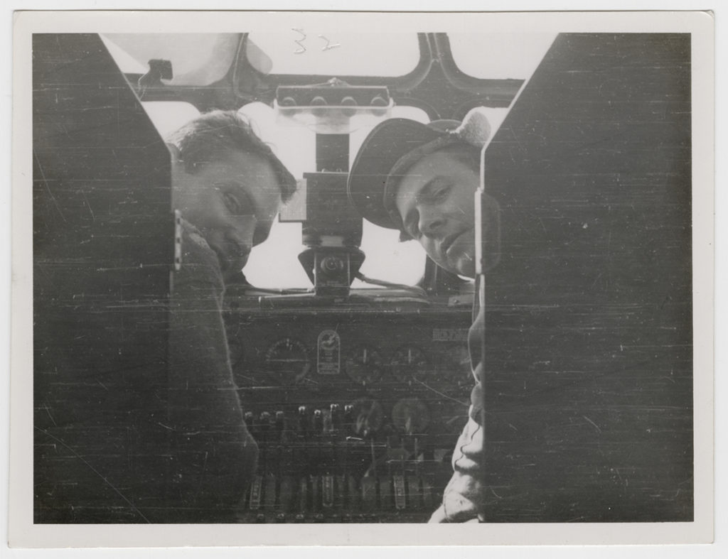 Photograph of two men in a B-24 bomber cockpit, ca. 1942–44. e_376th_0003