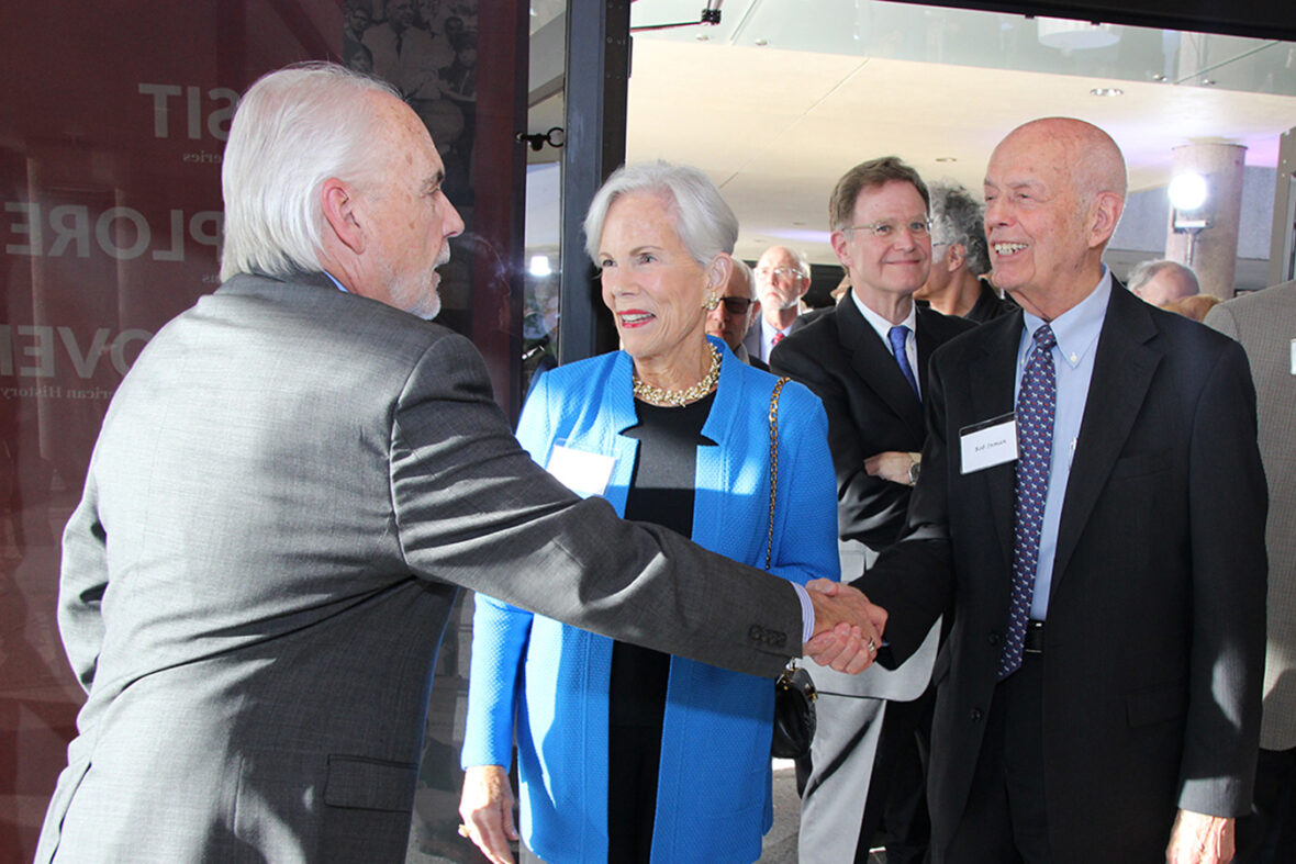 Don Carleton shaking hands with B. R. Inman with Nancy Inman next to her husband. Other guests are coming in through the center's entrance behind them.