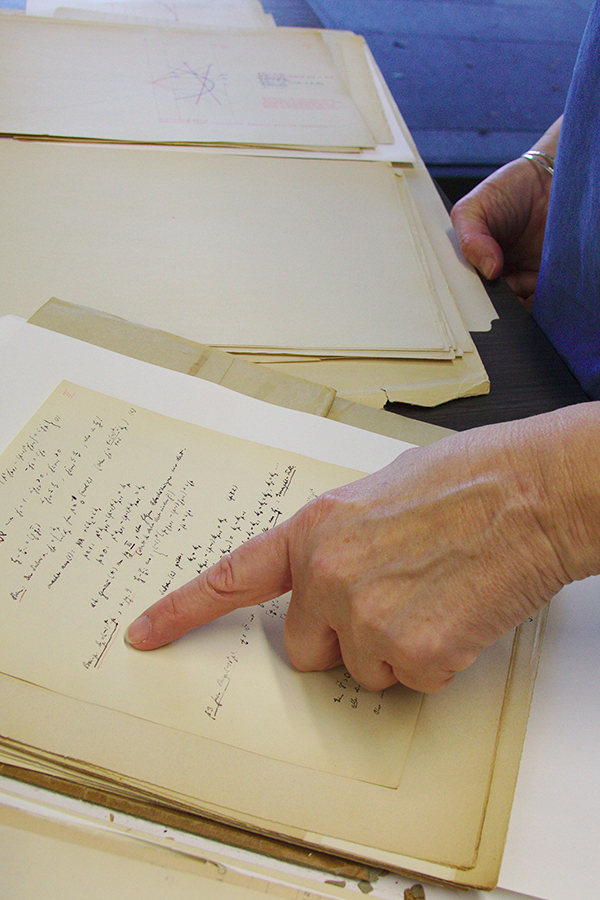 A hand pointing at a line of handwritten math equations on a page.