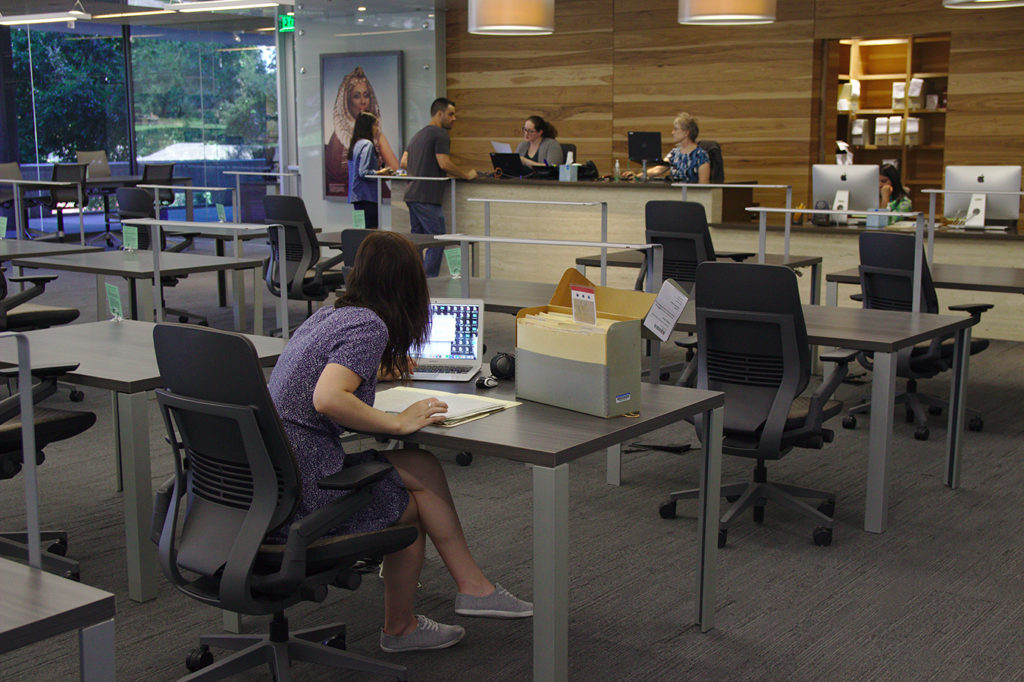 Female researcher sitting at a desk working on her computer with a box of artifacts. A couple stands at the reading room information desk conversing with Briscoe Center employee.