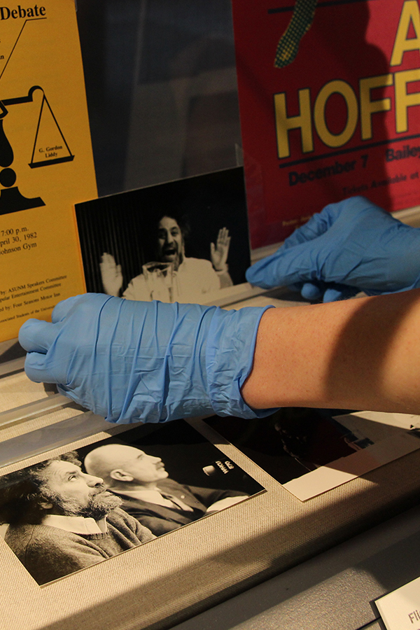 Hands in blue gloves putting a photograph of Abbie Hoffman among other artifacts in a display case.