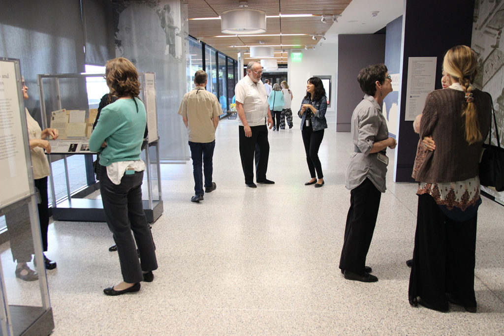 View from the end of the main hallway in the Briscoe Center. People are talking in groups, standing around artifact display cases.