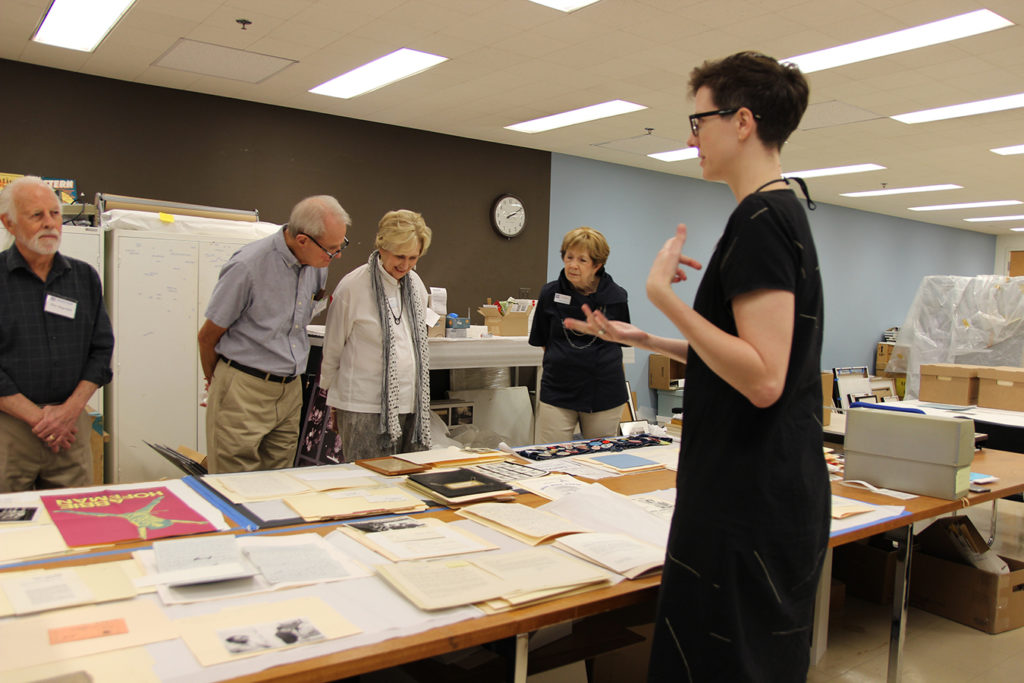 Sarah Sonner of the Briscoe Center leading a behind-the-scenes tour. Event guests are standing in front of a table with artifacts laid out.