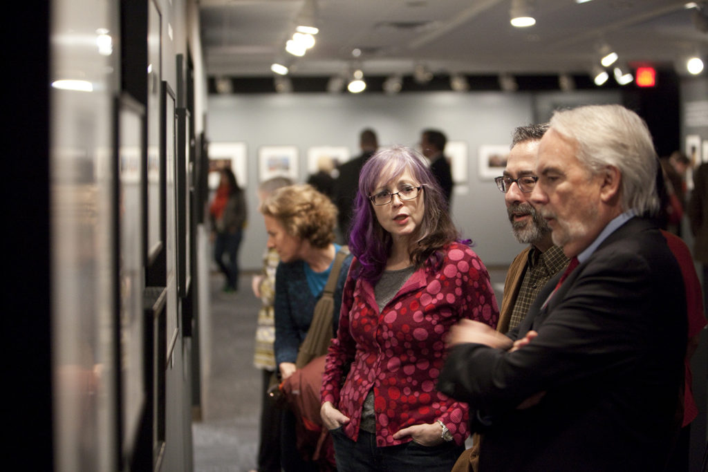 Don Carleton visits with guests while staring at a wall of photographs in an exhibition.