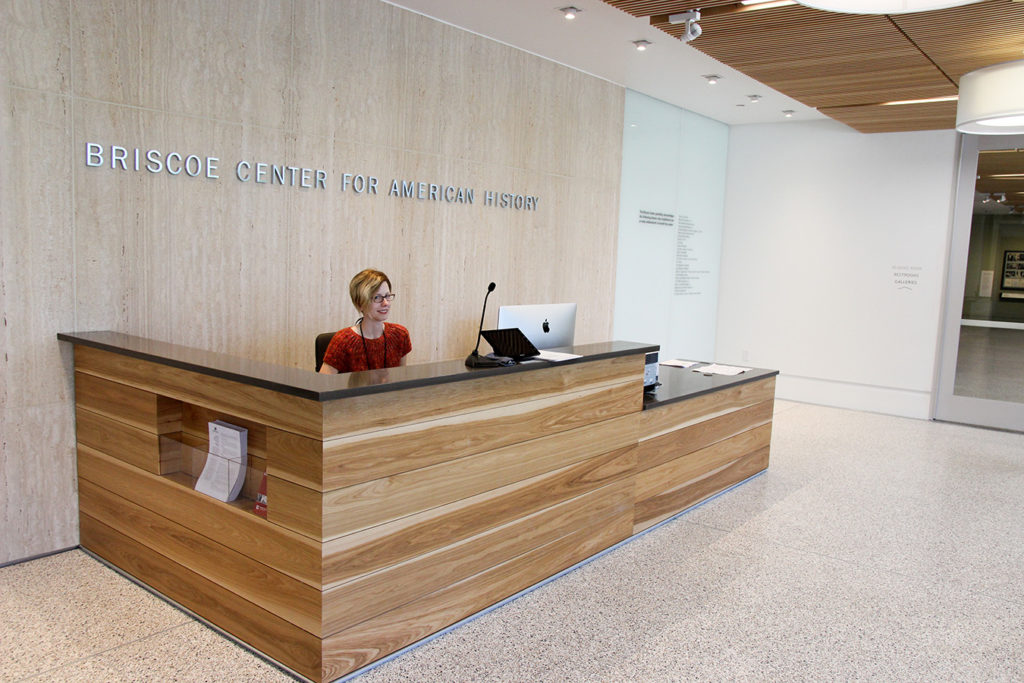 The Briscoe Center's welcome desk in the lobby with an employee staffed behind the desk.