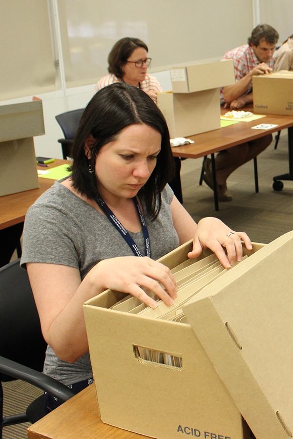 Researchers are going through archival boxes.