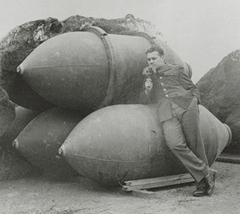 Andy Rooney smelling flowers while leaning against a stack of bombs, undated. Andy Rooney papers. di_11547