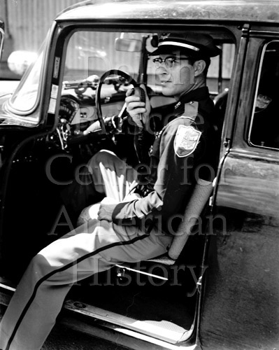 Kingsville policeman, Raymond Cruz, sitting in car talking on radio, March 1953. Jimmie A. Dodd Photograph Collection. e_jd_0022